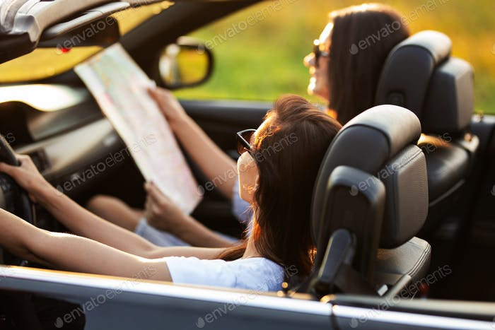 Two dark-haired young women in sunglasses are sitting in a black cabriolet on a sunny day. One of