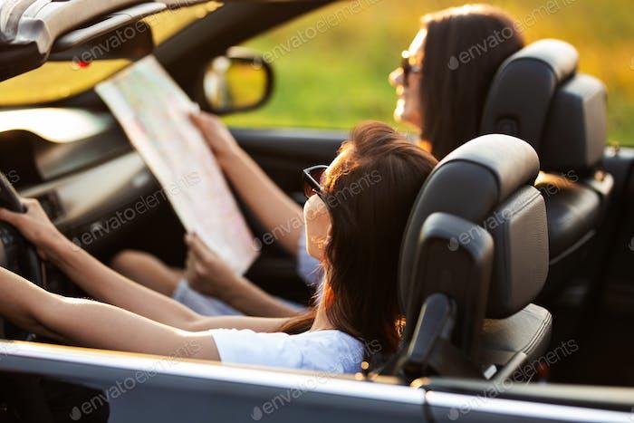 Zwei dunkelhaarige junge Frauen in Sonnenbrille sitzen an einem sonnigen Tag in einem schwarzen Cabriolet. Einer der