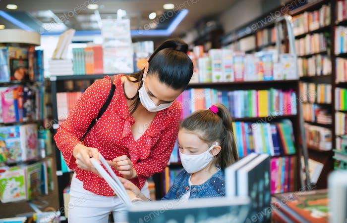Madre e hija con mascarilla de compras en la librería, concepto de coronavirus