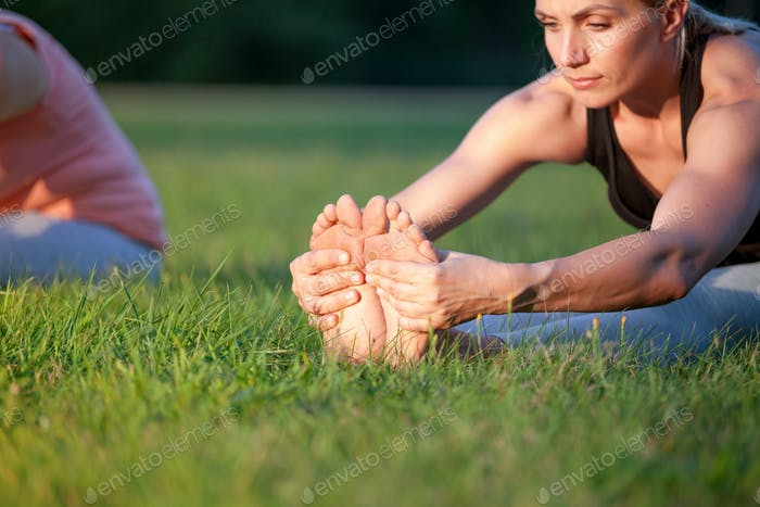 Yoga in the park, middle age woman stretching and holding feet close up