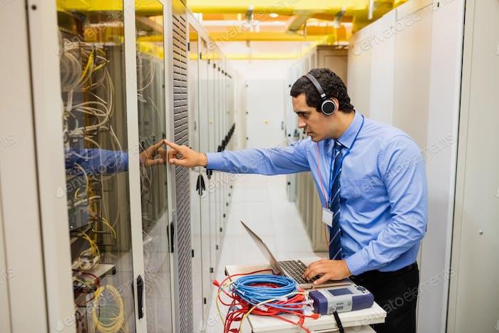 Technician in head phones using laptop