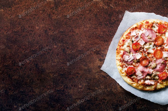 Fresh italian pizza with mushrooms, ham, tomatoes, cheese on on backing paper, dark background. Copy