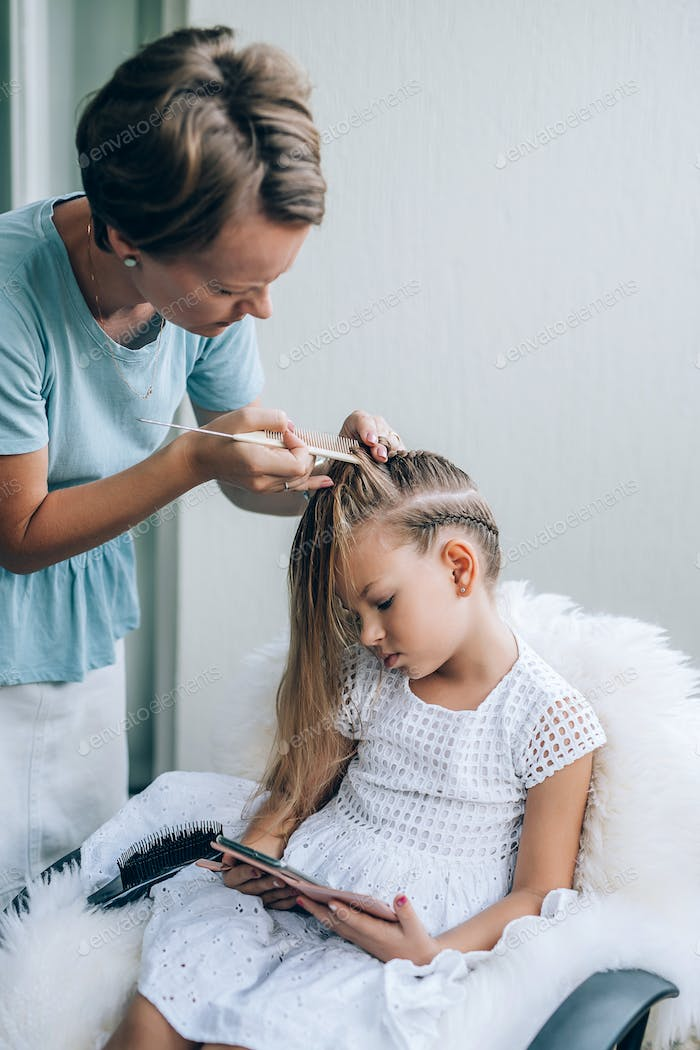 Mother does hair braid to her daughter, the girl is watching a cartoon on a mobile phone.