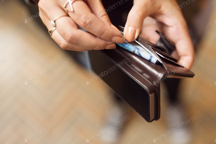 Woman holding open wallet with banknotes and cell phone
