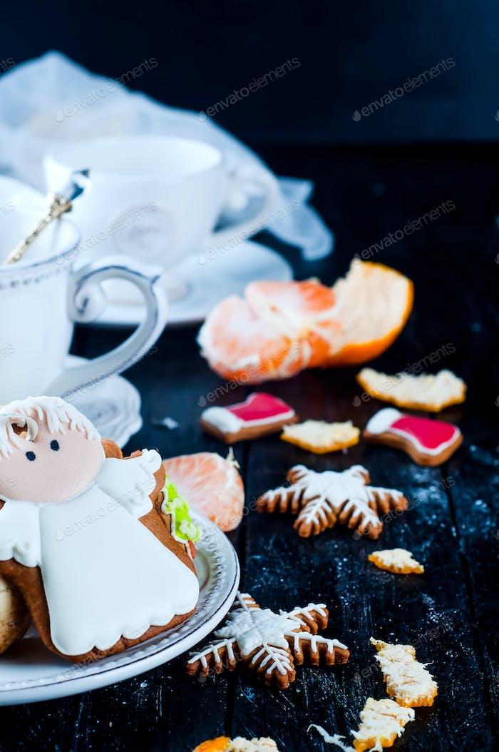 Teetasse mit Tee und Keksen Engel, Mandarineon ein schwarzer Tisch