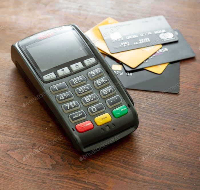Payment machine, POS terminal and credit cards on wooden desk