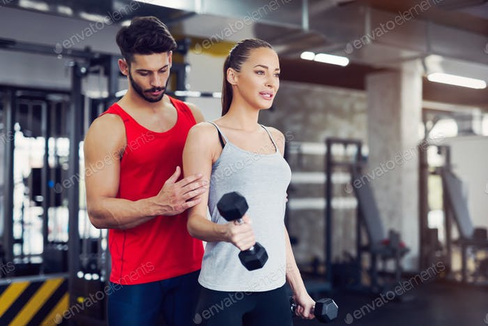 Junge erwachsene Frau trainieren im Fitnessstudio mit Trainer