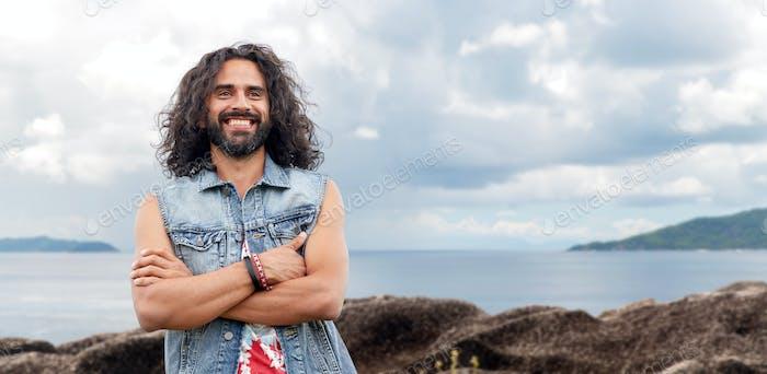 smiling hippie man in denim vest on island
