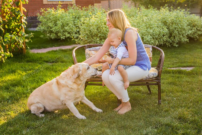 Mother holding baby son and playing with labrador dog in the park