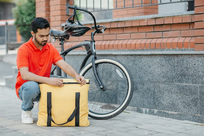 Accurate delivery. Busy bearded courier zips up large yellow bag, beside a bicycle
