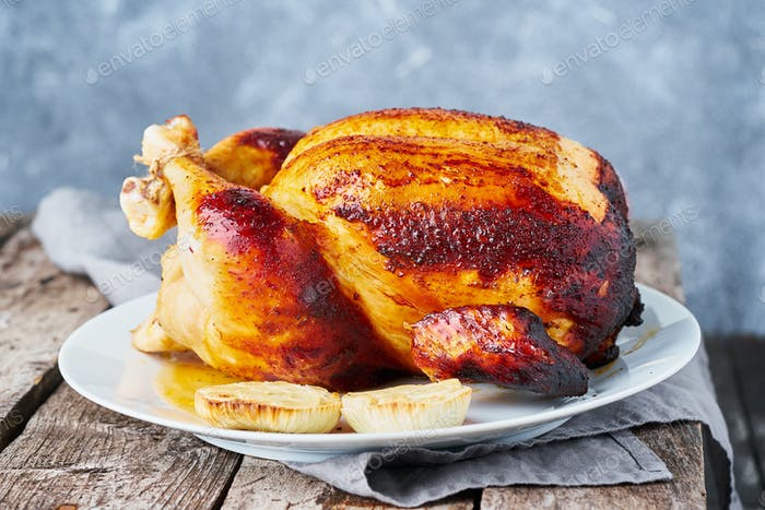 Grilled chicken in blue casserole on dark gray old wooden table,