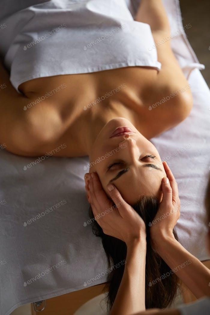 Head and face massage in spa salon
