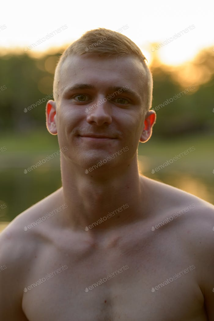 Young man with blond hair shirtless at the park outdoors