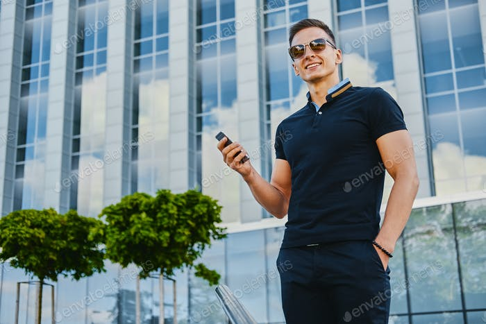 A man using smartphone over modern building background.