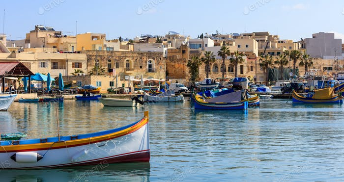 Marsaxlokk fishermen village in Malta. Traditional colorful boats at the port of Marsaxlokk