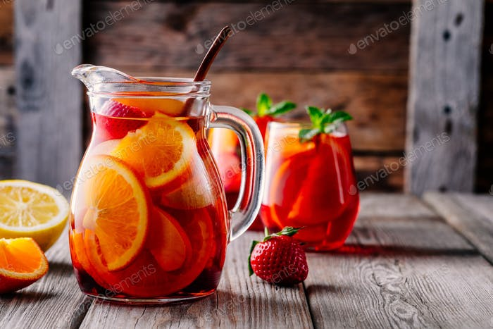 Homemade red wine sangria with orange, apple, strawberry and ice in pitcher  and glass
