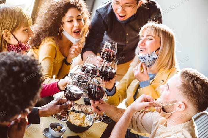 Happy friends wearing protective face masks toasting red wine sitting at restaurant