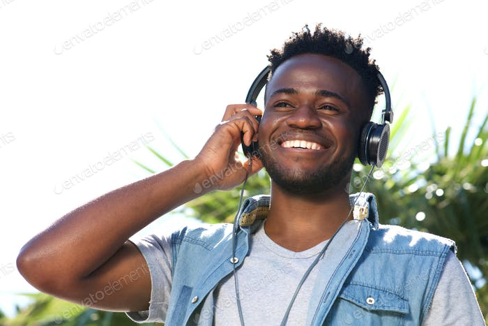 Close up happy young black man listening to music with headphones