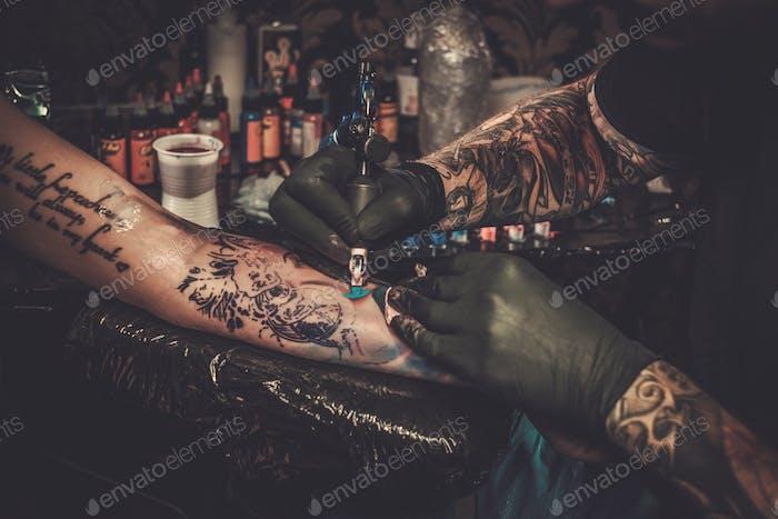 Профессиональный тату-художник делает татуировку на руке молодой девушки.