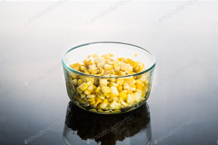 Corn kernels in transparent glass bowl  in dark reflective backg