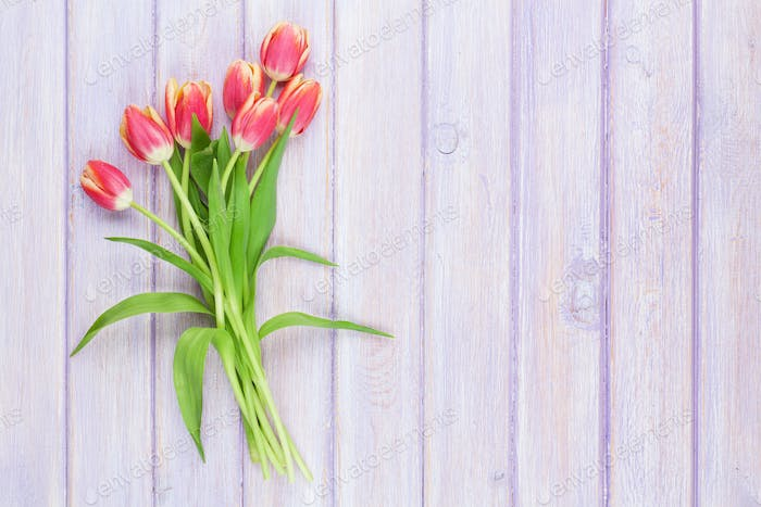 Red tulips over purple wooden table