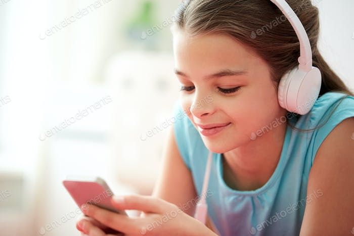 close up of girl with smartphone and headphones