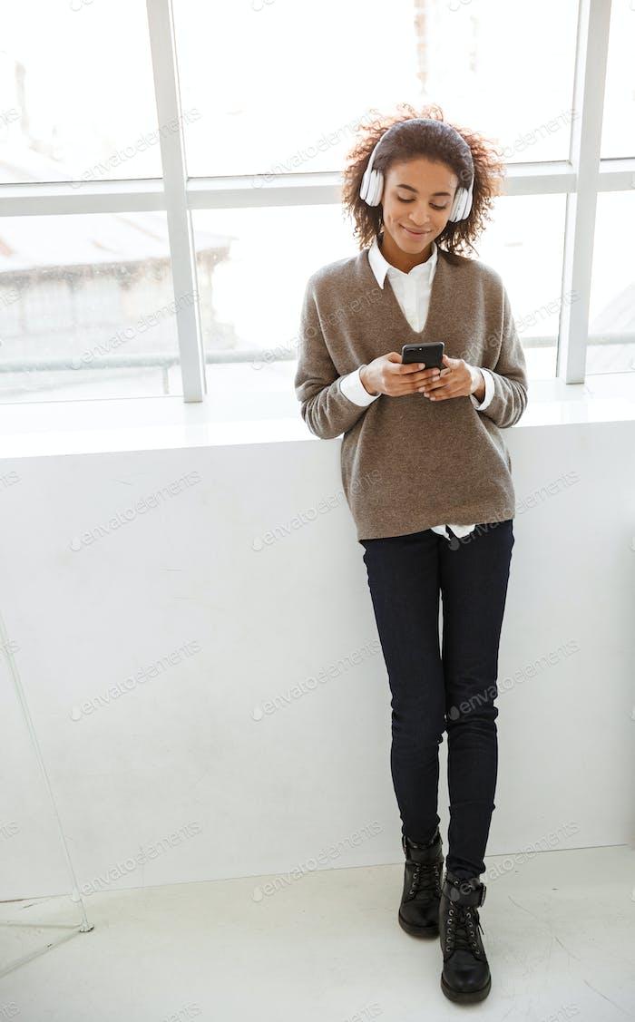 Портрет женщины, слушая музыку с наушниками и мобильным телефоном в комнате