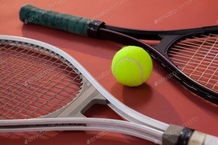 Hochwinkelansicht des fluoreszierenden gelben Balls inmitten von Tennisschlägern