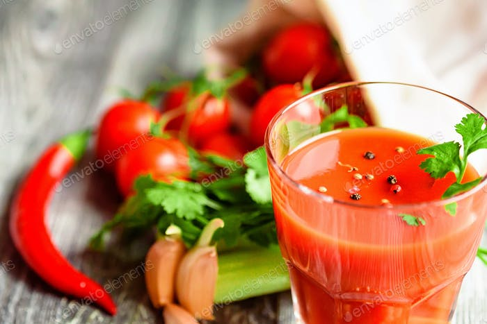 Glass of tomato juice with fresh tomatoes