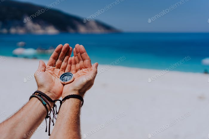 Open hand palms holding metal compass against sandy beach and blue sea. Searching your way concept