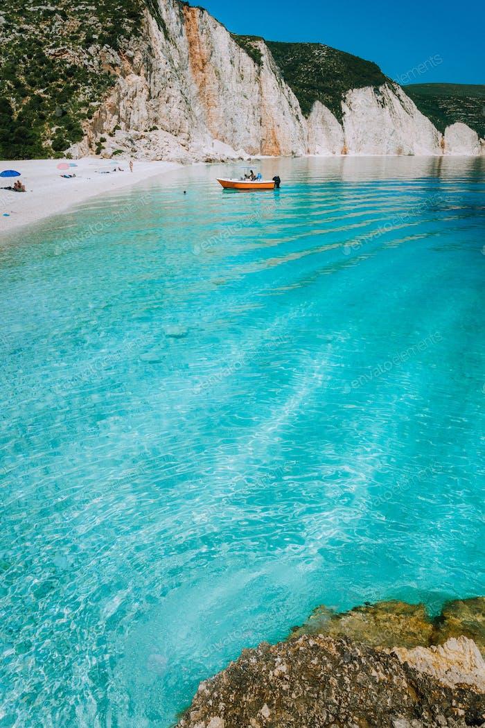 Tourist Vergnügungsboot Land zu schönen abgelegenen weißen Kiesstrand mit gewellten transparenten klar