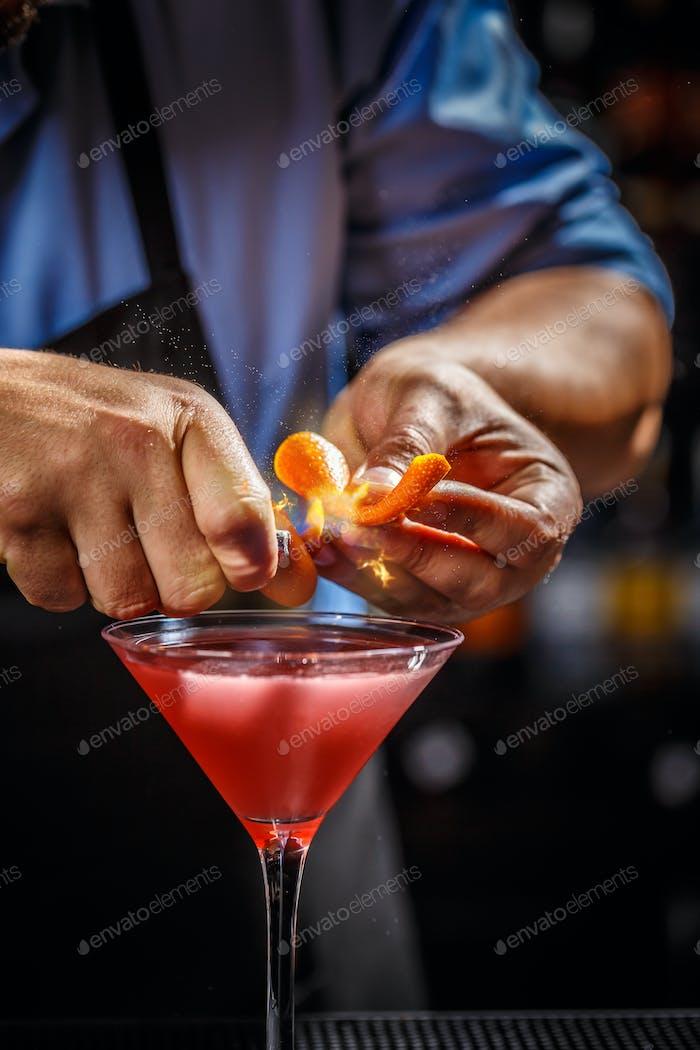 Barman schmückt kosmopolitischen Cocktail