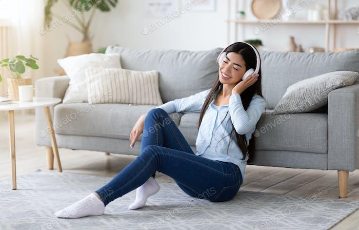 Entspannende Playlist. Junge asiatische Mädchen Musik hören In Wireless Kopfhörer Zu Hause