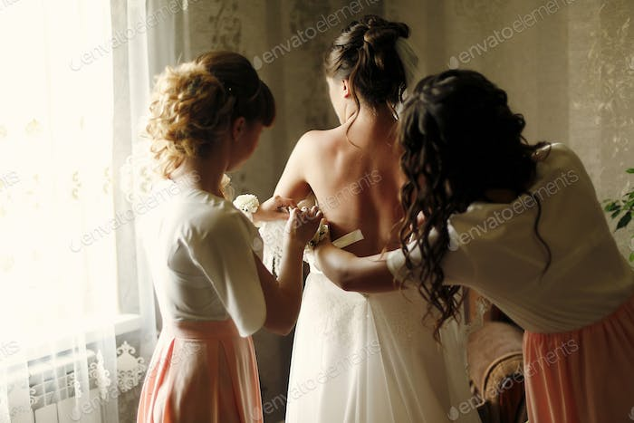 beautiful bridesmaids in pink dresses helping bride get dressed in gown in the morning
