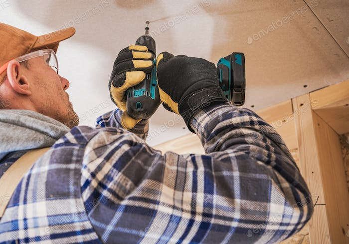 Contractor Assembling Drywall Board Using Drill Driver
