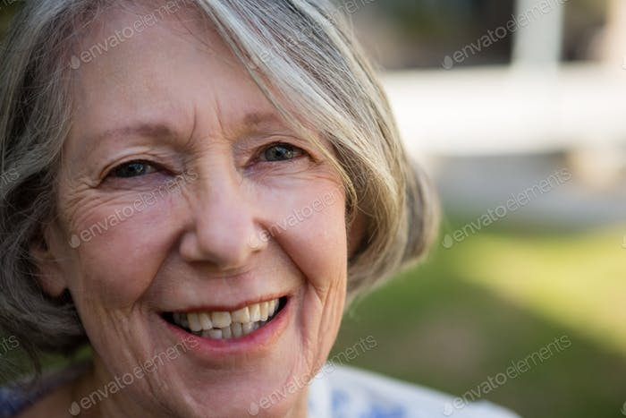 portrait of cheerful senior woman standing in park