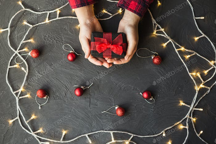 Female hands holding New Year or Christmas present on black background.