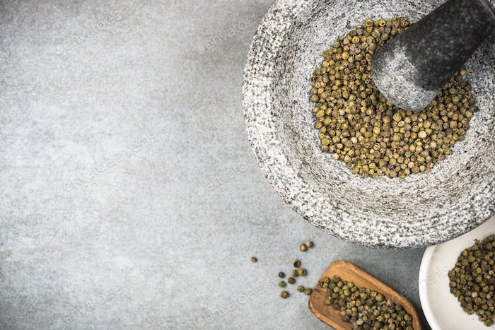 Green peppercorn seed in granite mortar or pestle