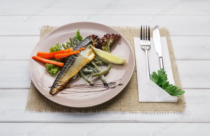 Restaurant food on wooden table. Smoked mackerel with vegetables