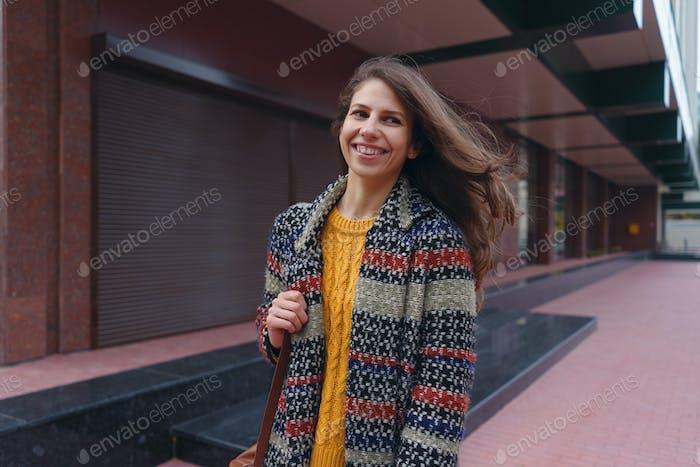 Stilvolle junge Frau spaziert in der Stadt