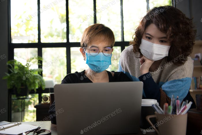 Two Asian businesswomen wearing surgical mask
