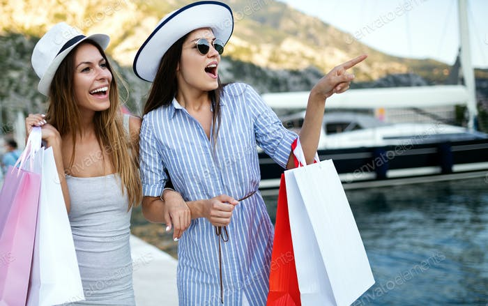 Happy young attractive girls with shopping bags in the city