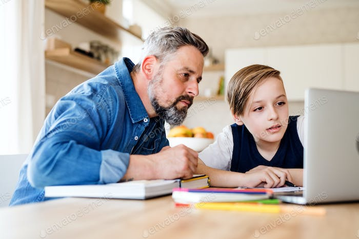 Mature father with small son sitting at table indoors, using laptop