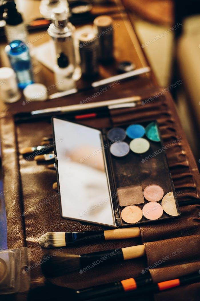 makeup set of brushes, powder, eyeshadows on table