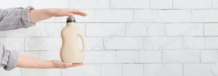 Woman holding eco friendly washing detergent with natural softener