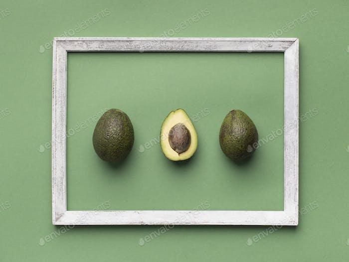Avocado inside wooden border in minimalism style on green