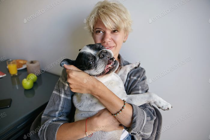 Attractive young lady with short blond hair holding and embracing her adult dog