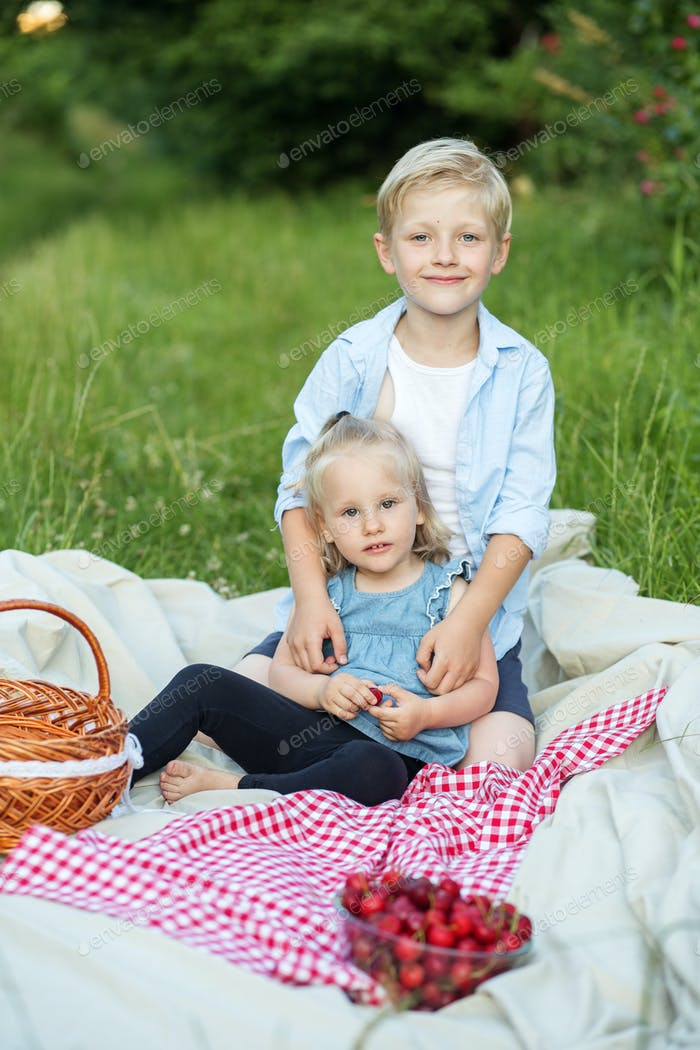 Children, a boy and a girl eat cherries in nature.
