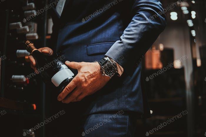 Eleganter Mann im Anzug im Weinkeller mit Flasche Wein