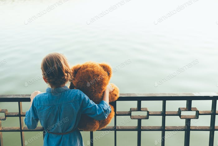 Girl embracing a cute teddy bear looking to lake